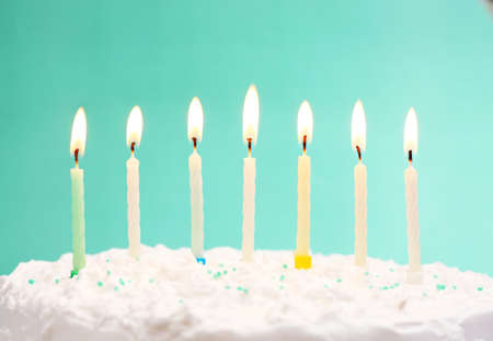 blue candles: Birthday cake with candles on color background Stock Photo