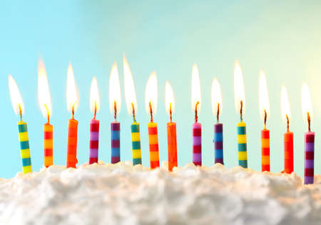 lit candle: Birthday cake with candles on color background Stock Photo