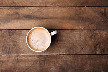 Šálek kávy na dřevěný stůl, pohled shora Reklamní fotografie