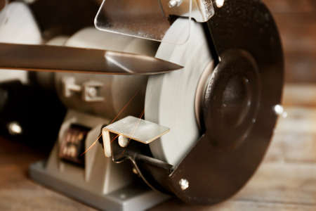 sharpening process: Knife sharpener on wooden table, closeup Stock Photo