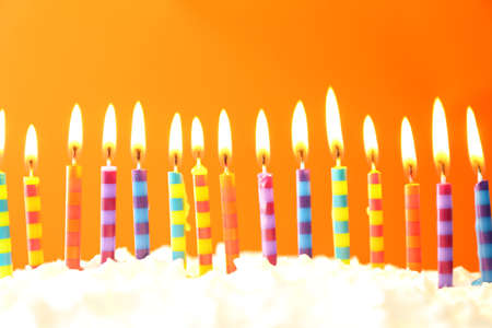 orange color: Birthday cake with candles on color background Stock Photo