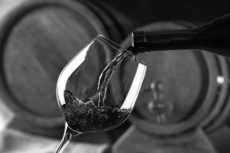 stylization: Pouring red wine from bottle into glass,  black and white retro stylization