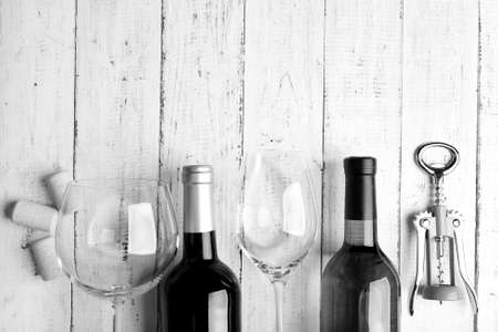 stylization: Bottles of wine, glass and corkscrew on wooden table,  black and white retro stylization