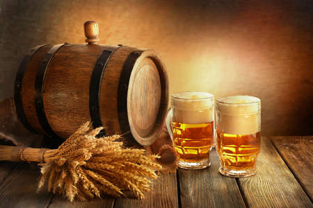 mug: Beer barrel with beer glasses on table on brown background Stock Photo