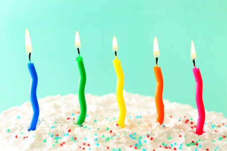 eating cake: Birthday cake with candles on color background Stock Photo