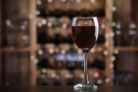 Glass of red wine on bar background