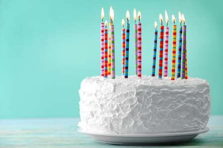 glücklich: Geburtstagstorte mit Kerzen auf farbigem Hintergrund