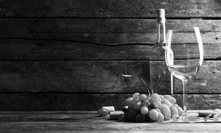 Bottle and glass of wine with grape on wooden background,  black and white retro stylization