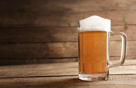 unbottled: Glass of beer on wooden background
