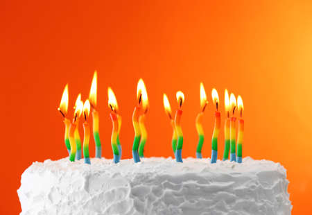 birthday background: Birthday cake with candles on color background Stock Photo