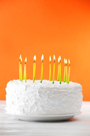 Birthday cake with candles on color background Stock Photo