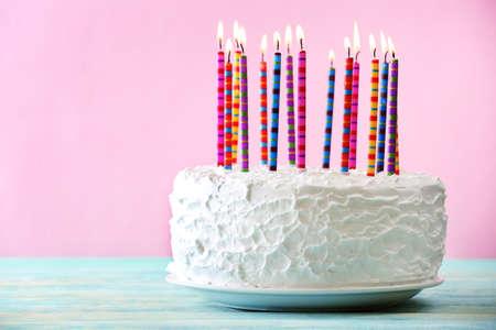 torta: Torta de cumpleaños con velas en el fondo de color Foto de archivo