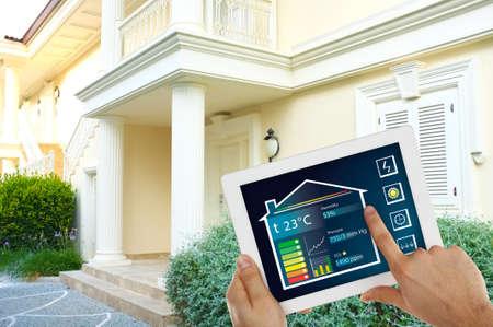 case moderne: Controllore energia intelligente o il controllo remoto delle abitazioni in linea sul tablet-pc Archivio Fotografico