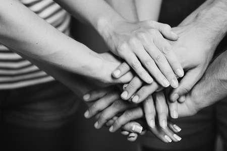 trabajo en equipo: Manos unidas de cerca. Blanco y negro estilización retro
