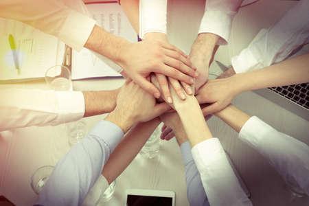 profesionistas: Manos unidas de equipo de negocios sobre fondo de la vista del espacio de trabajo superior