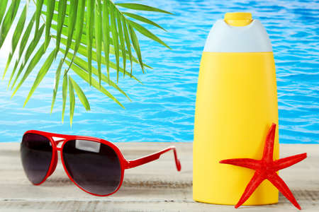 summer background: Bottle of suntan cream with sunglasses and sea star on table on water background