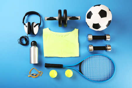 group objects: Sports equipment and T-shirt on color table, top view