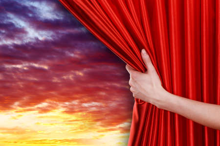 cloude: Human hand opens red curtain on sky background