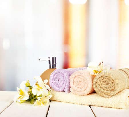 champú: Toallas suaves con dosificador y flores en el baño Foto de archivo