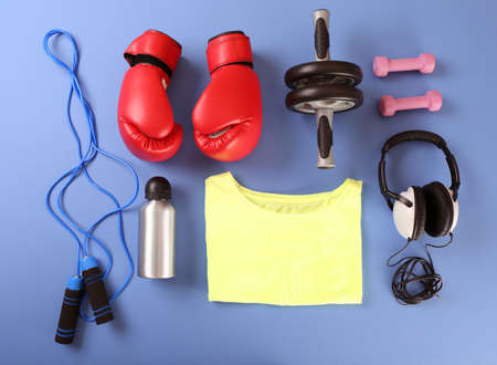 equipment: Sports equipment and T-shirt on color table, top view