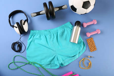 exercise equipment: Sports equipment and shorts on color table, top view