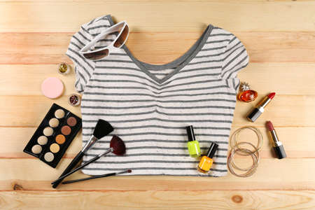 teen: Female shirt and cosmetics on wooden table, top view