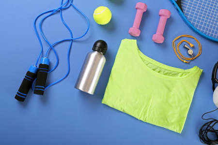 sports clothing: Sports equipment and T-shirt on color table, top view