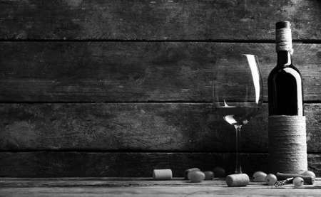 stylization: Bottle and glass of wine with grape on wooden background,  black and white retro stylization