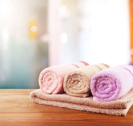white towels: Rolled bath towels on wooden table in bathroom