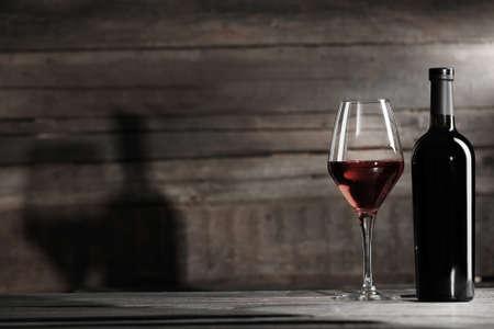 bouteille de vin: Bouteille de vin avec un verre sur fond de bois, noir et blanc rétro stylisation