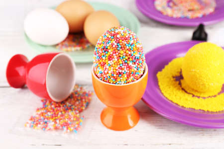 colorful beads: Decoration Easter eggs with colorful beads on wooden table, closeup Stock Photo
