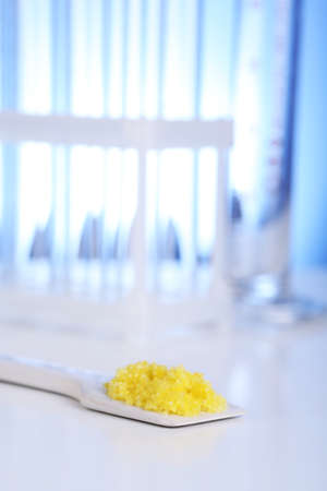 granules: Laboratory spatula with granules on blue background