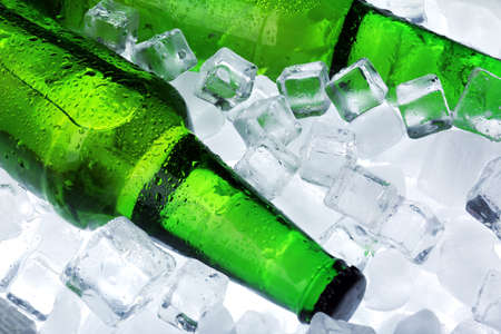 dew cap: Glass bottles of beer on ice cubes background Stock Photo