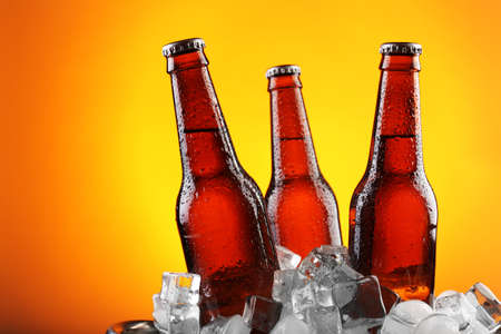 cold background: Glass bottles of beer in ice cubes on color background Stock Photo