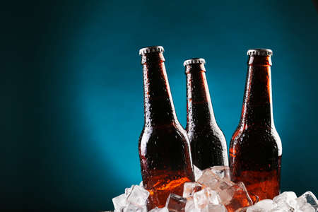 Glass bottles of beer in ice cubes on color background Stockfoto