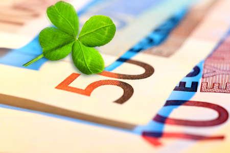 Clover leaf and euros, close-up