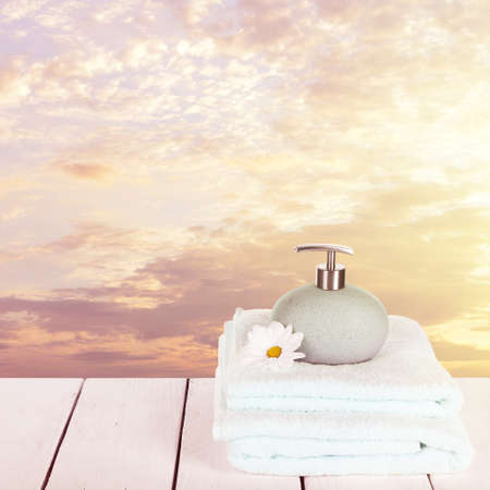 sunshine background: Soft towels with dispenser and flowers on sky background Stock Photo