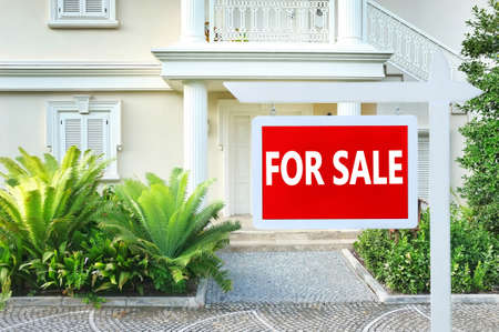 estate: Real estate sign in front of new house for sale Stock Photo
