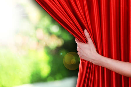 curtain: Human hand opens red curtain on nature background