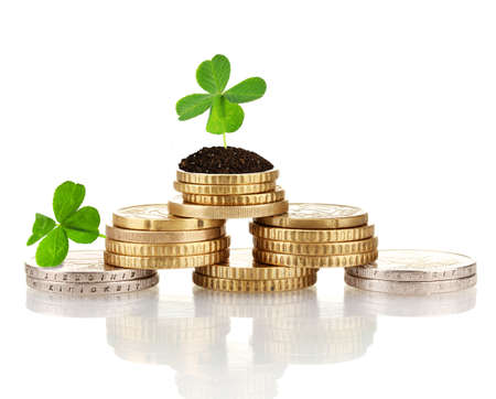 Clover leaf growing out on coins isolated on white Stock Photo
