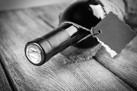 Wijnfles gewikkeld in jute doek op houten tafel, zwart en wit retro stilering Stockfoto