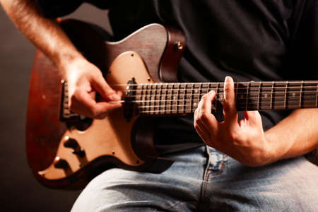 guy playing guitar: Young musician playing electric guitar close up