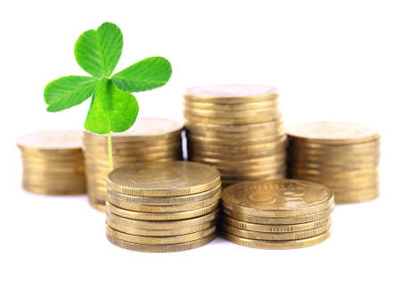 quarterfoil: Clover leaf growing out of coins isolated on white