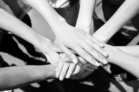 hand by hand: United hands outdoors.  Black and white retro stylization