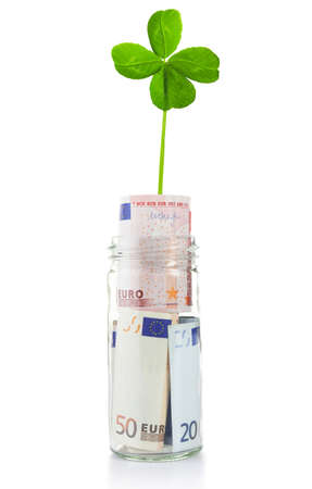 Euro banknotes in glass jar with clover leaf isolated on white