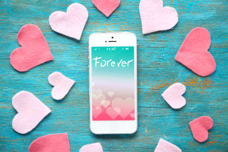 romantic heart: White smart phone with hearts on wooden desk. Stock Photo