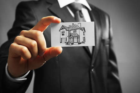 property agent: Businessman with house picture, concept real estate