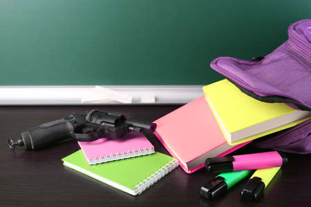 bookbag: Gun in school backpack on wooden desk, on blackboard background