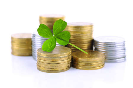 winning stock: Clover leaf and stacks of coins isolated on white