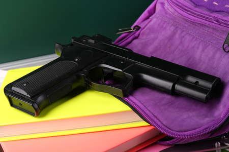 pistola: Pistola en la mochila escolar de primer plano, en el fondo pizarra